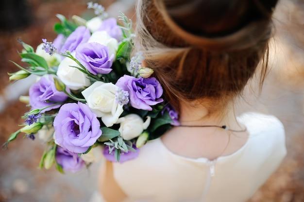 Menina segurando um buquê de flores brancas e roxas