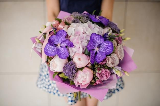 Menina segurando um buquê roxo de flores nas mãos