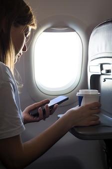 Menina segurando um café e olhando para o telefone