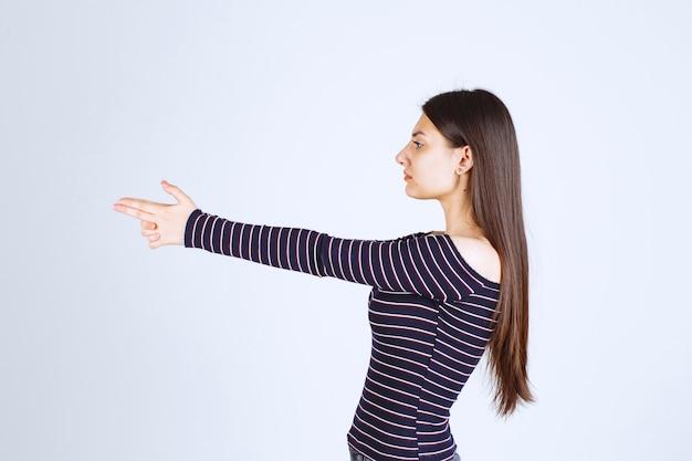 Menina segurando um cartaz de arma de mão.