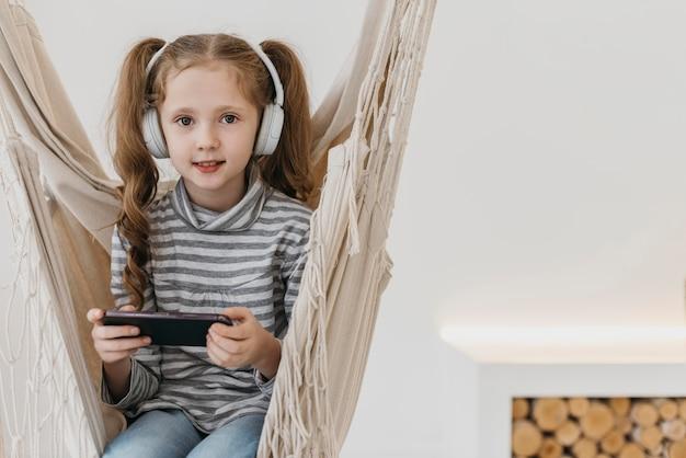 Menina segurando um celular e usando fones de ouvido