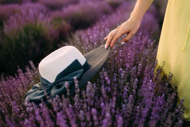 Menina segurando um chapéu de palha preto e branco sobre arbustos de lavanda