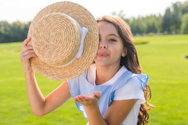 Menina segurando um chapéu enquanto sopra beijos