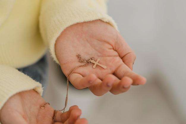 Menina segurando um colar de cruz nas mãos
