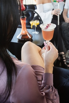 Menina segurando um copo com um coquetel de laranja decorado com rosa seca, as bebidas são decoradas
