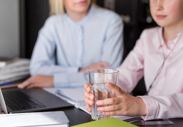 Menina segurando um copo de água