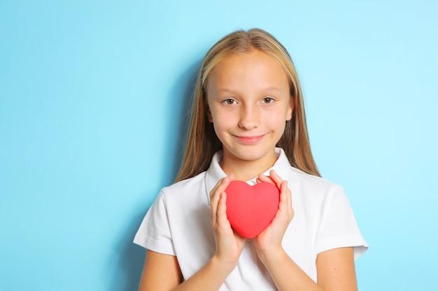 Menina segurando um coração vermelho nas mãos sobre um fundo azul