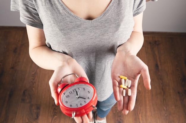 Menina segurando um despertador e um remédio na mão