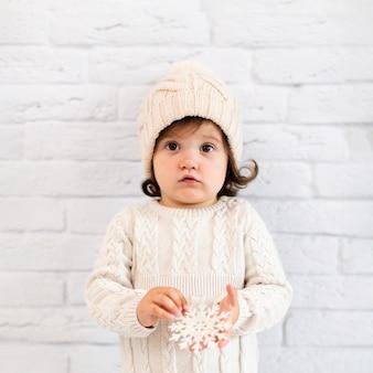 Menina segurando um floco de neve e olhando para o fotógrafo