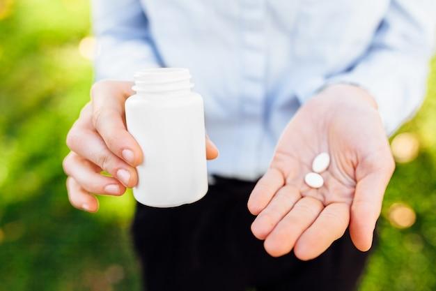 Menina, segurando um frasco de comprimidos nas mãos dela, ao ar livre