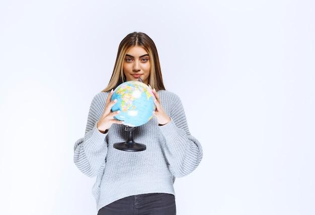 Menina segurando um globo do mundo e promovendo-o.