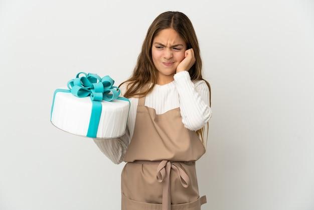 Menina segurando um grande bolo sobre um fundo branco isolado frustrada e cobrindo as orelhas