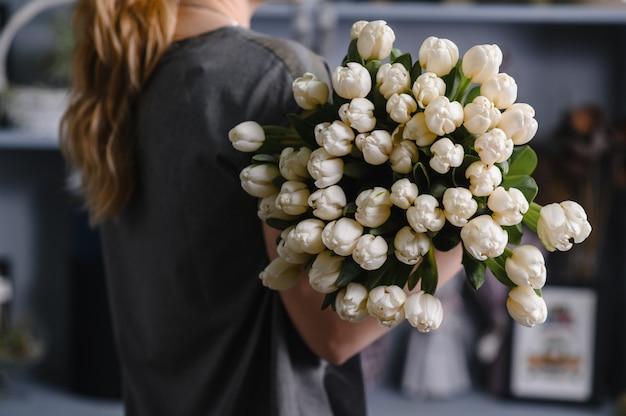 Menina, segurando um grande buquê de tulipas nas mãos dela