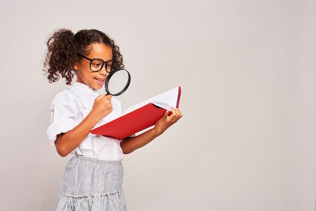 Menina segurando um grande livro e uma lupa