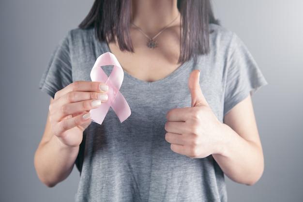Menina segurando um ícone de câncer e com a outra mão mostra um gesto ok