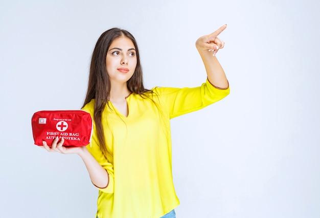 Menina segurando um kit vermelho de primeiros socorros e apontando para alguém.