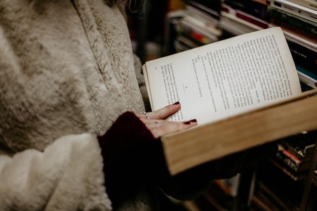Menina, segurando um livro aberto nas mãos nas livrarias. conceito de leitura.