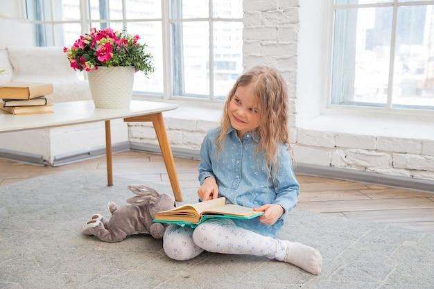 Menina segurando um livro e sorrindo enquanto está sentada no chão da sala de estar