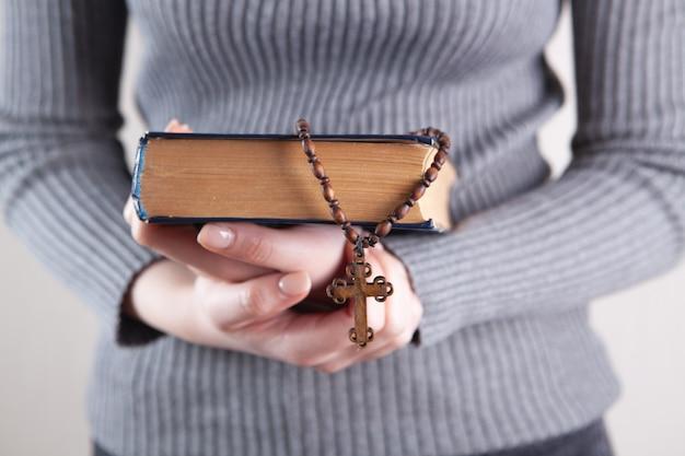 Menina segurando um livro e uma cruz