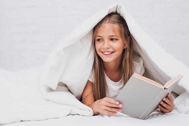 Menina segurando um livro enquanto olhando para longe