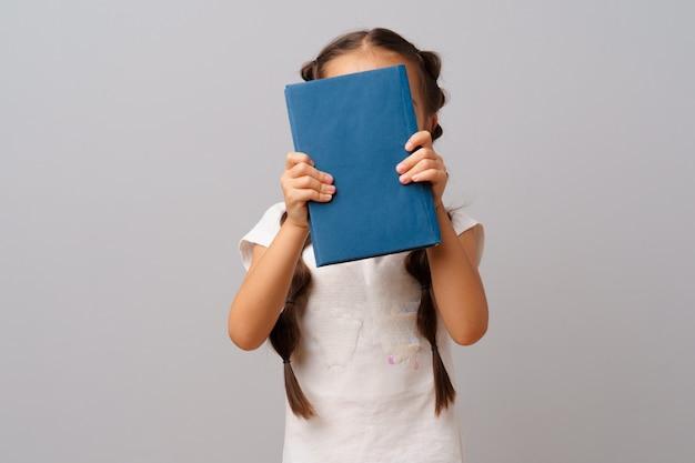 Menina, segurando um livro nas mãos dela