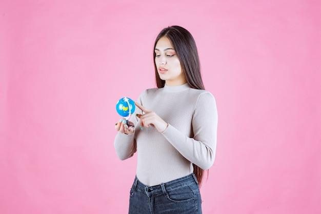 Menina segurando um mini globo e estudando-o atentamente Foto gratuita