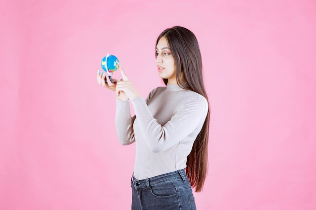 Menina segurando um mini globo e estudando-o atentamente