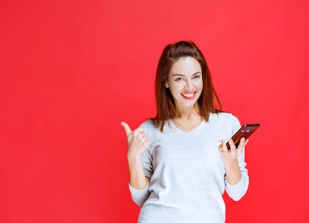 Menina segurando um novo modelo preto smartphone e se sentindo positiva e satisfeita.