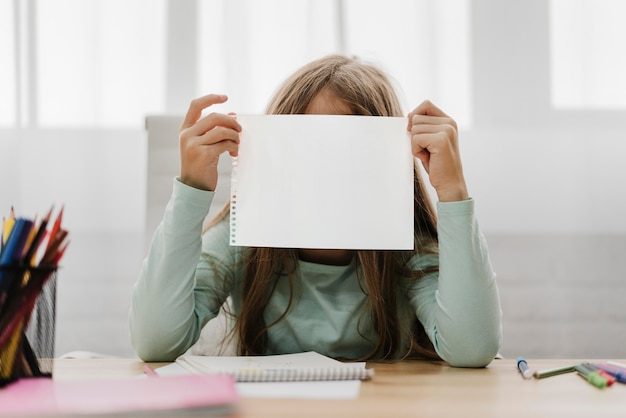 Menina segurando um papel em branco na frente dela