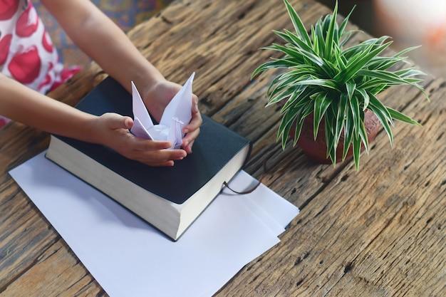 Menina segurando um pássaro de origami branco nas mãos