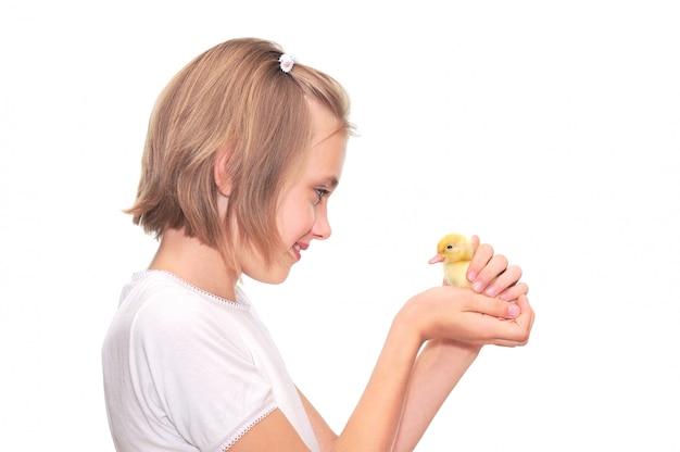 Menina segurando um patinho isolado no branco