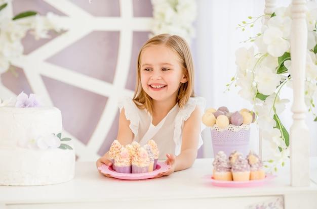 Menina, segurando um prato rosa com bolos doces na barra de chocolate