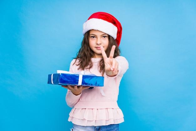 Menina segurando um presente comemorando o dia de natal