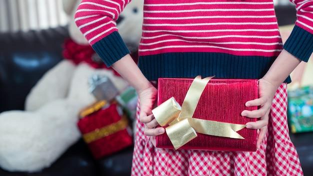 Menina segurando um presente de natal de papel de embrulho de glitter vermelho escondido para surpreender.