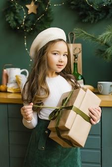 Menina segurando um presente de natal em uma boina bege, blusa bege e saia turquesa. desembalando um presente de natal