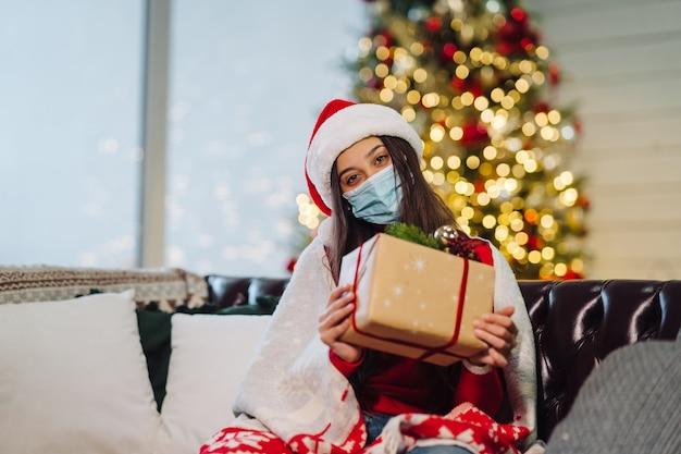 Menina segurando um presente de natal na véspera de ano novo.