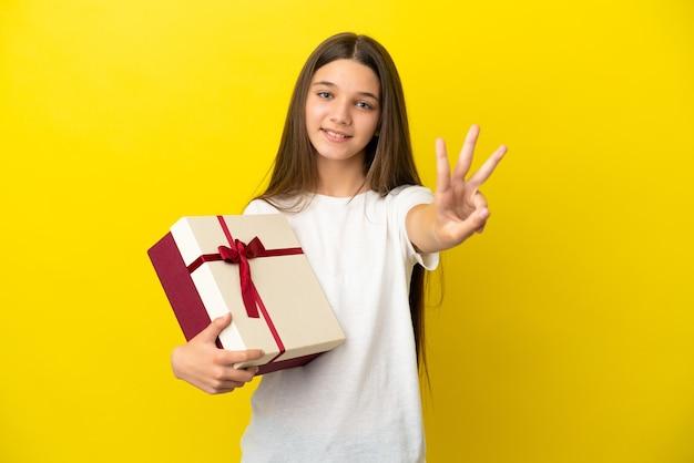 Menina segurando um presente sobre um fundo amarelo isolado feliz e contando três com os dedos