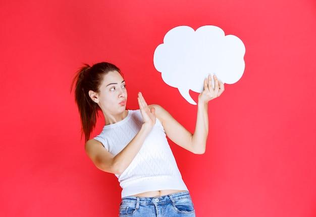 Menina segurando um quadro de ideias de forma de nuvem em branco e se recusando a jogá-lo.