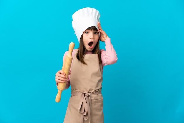 Menina segurando um rolo de massa isolado em um fundo azul com expressão de surpresa