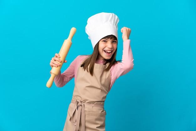 Menina segurando um rolo de massa isolado em um fundo azul, comemorando uma vitória