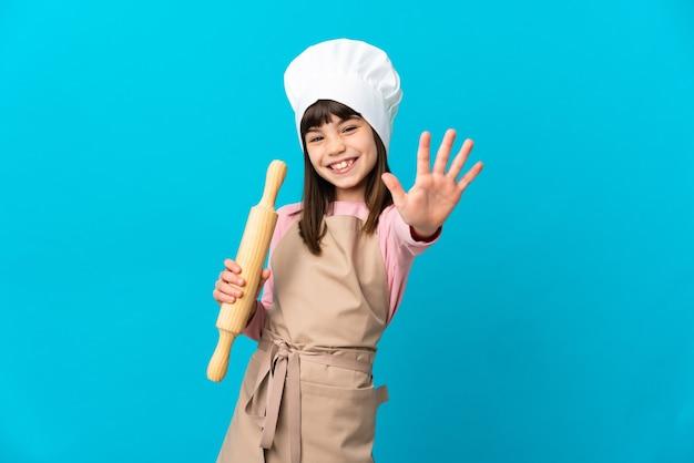Menina segurando um rolo de massa isolado em um fundo azul, contando cinco com os dedos