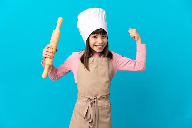 Menina segurando um rolo de massa isolado em um fundo azul fazendo um gesto forte