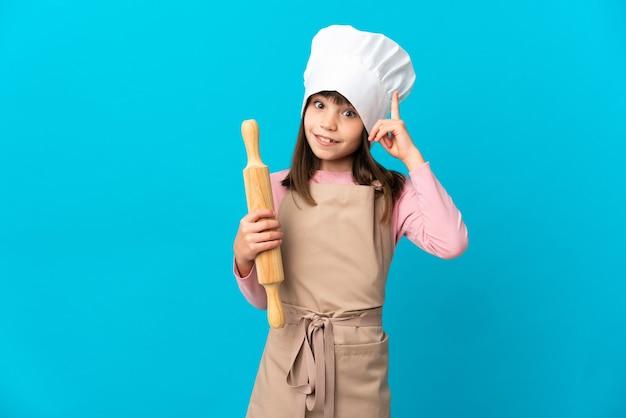 Menina segurando um rolo de massa isolado em um fundo azul, pensando em uma ideia