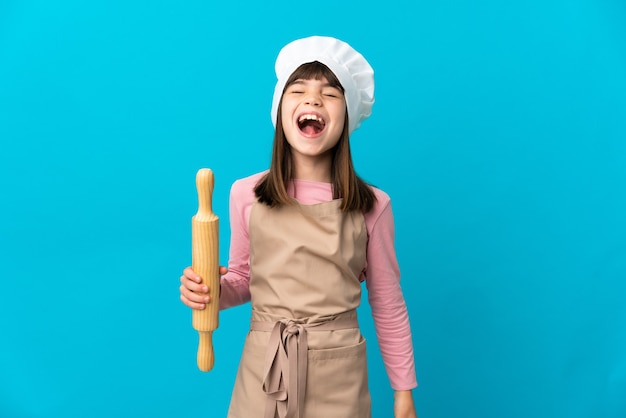 Menina segurando um rolo de massa isolado em um fundo azul rindo