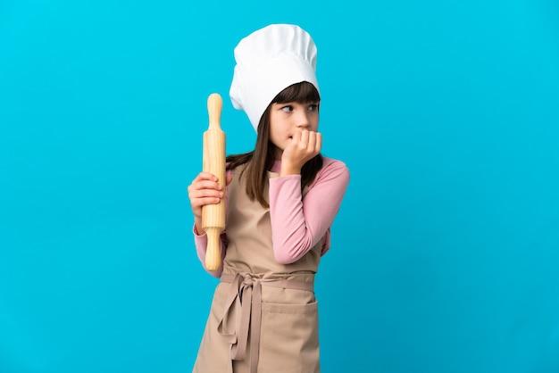 Menina segurando um rolo de massa isolado na parede azul, tendo dúvidas