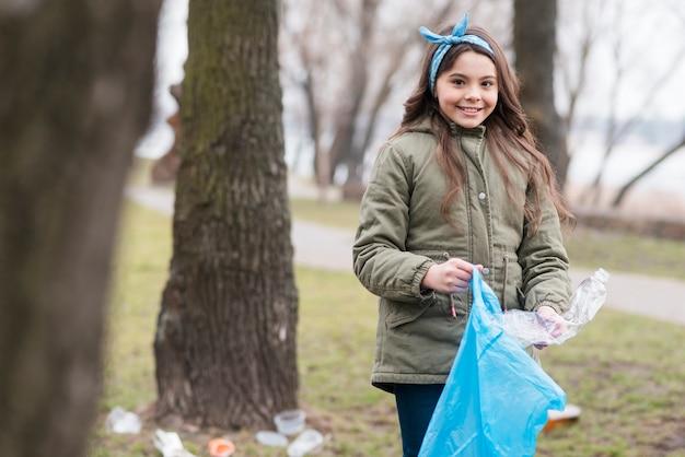 Menina segurando um saco de plástico para reciclagem