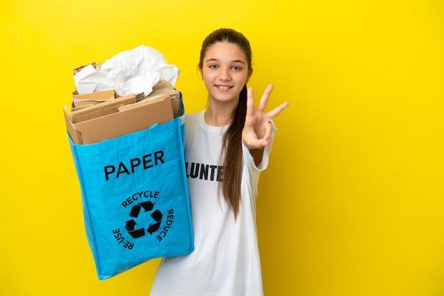 Menina segurando um saco de reciclagem cheio de papel para reciclar sobre um fundo amarelo isolado feliz e contando três com os dedos