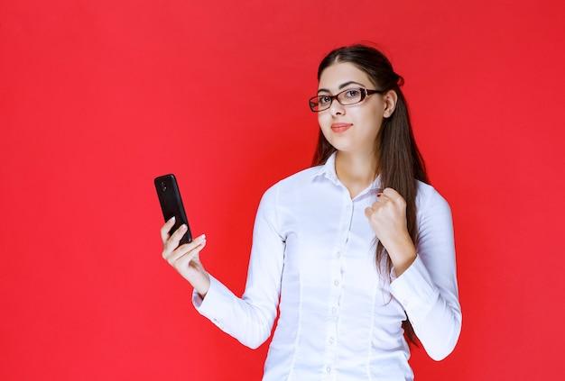 Menina segurando um smartphone e dando poses de felicidade.