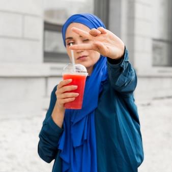 Menina segurando um smoothie enquanto faz o sinal da paz
