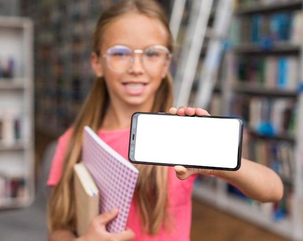 Menina segurando um telefone de tela vazia na biblioteca